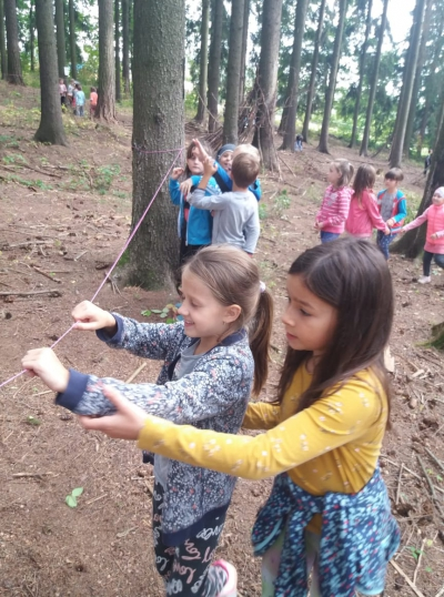 Děti s družinou v lese plní úkoly