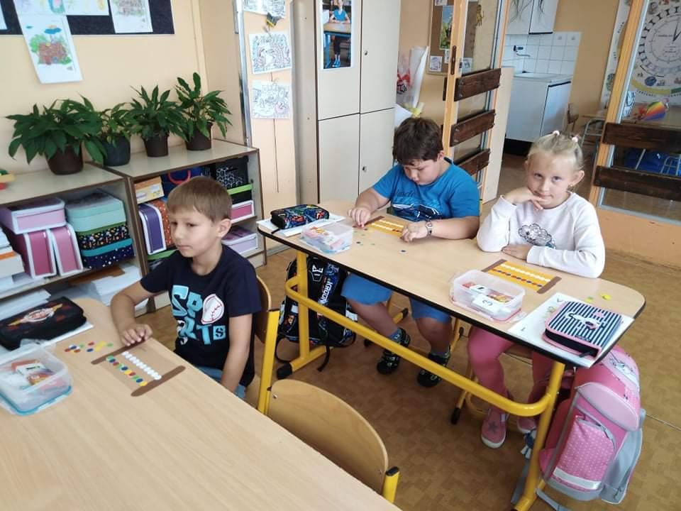Prvňáci v hodině matematiky s počítadly