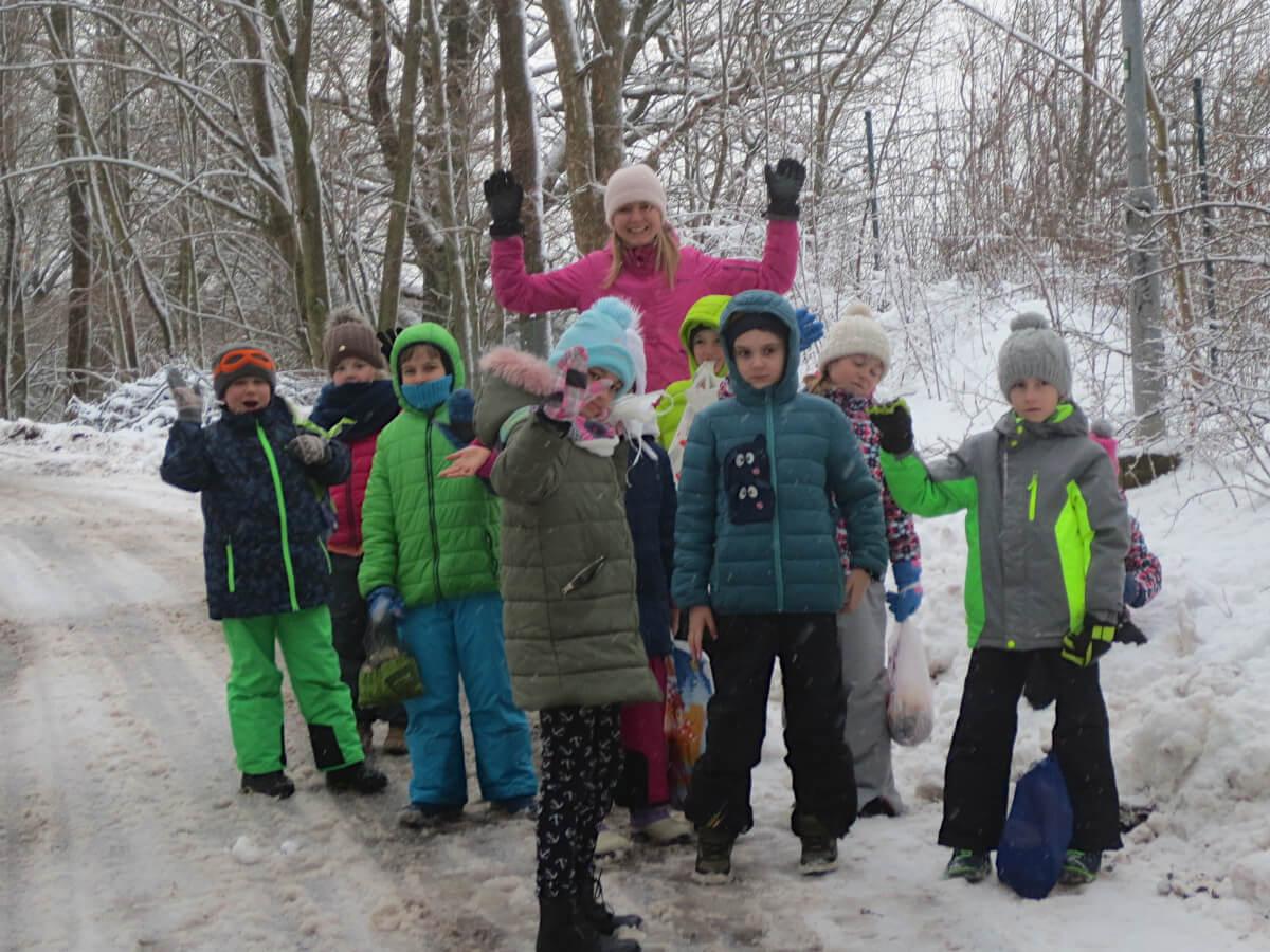 Žáci druhých tříd v lese s jídlem pro zvířátka