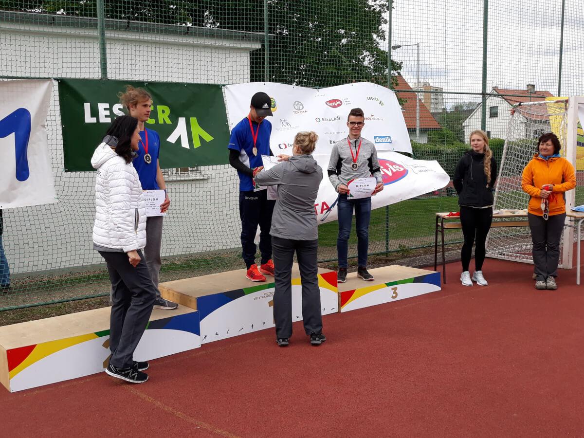 Krajské kolo Odznaku všestrannosti. Žák ZŠ Mládežnická stojí na stupních vítězů a přebírá od Šárky Kašpárkové bronzovou medaili.
