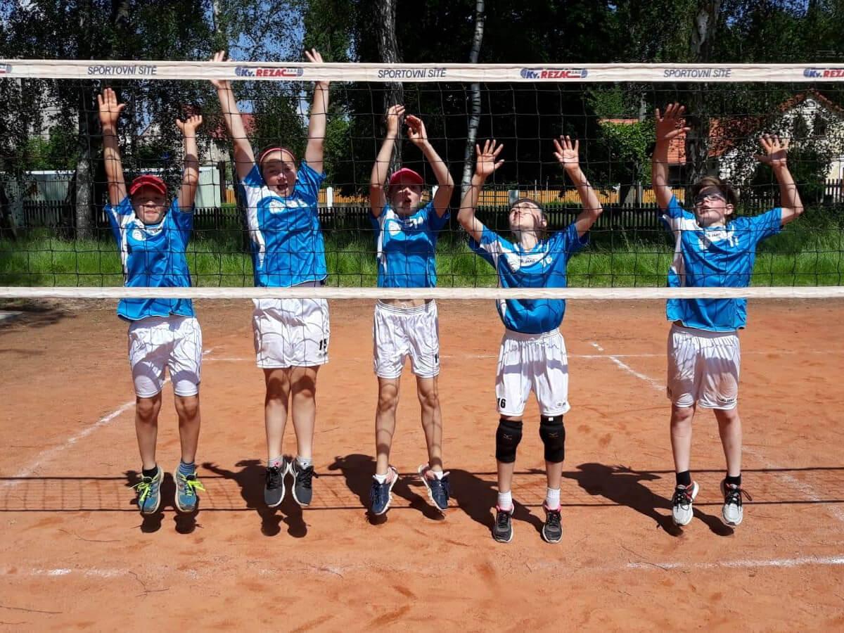 Volejbalový turnaj. Hráči ve výskoku u sítě, oslavují úspěch.