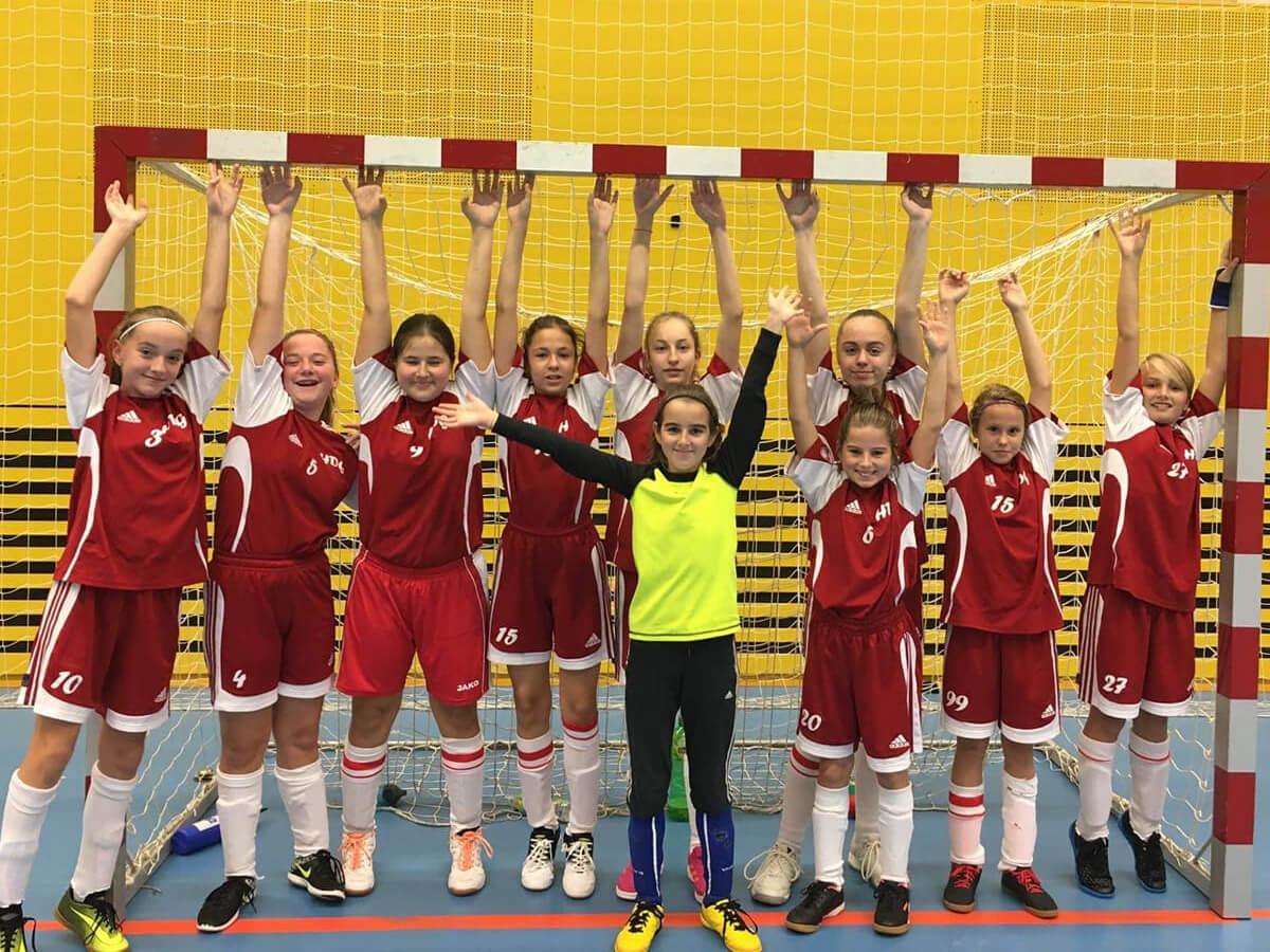 Vítězné družstvo dívek ze ZŠ Mládežnická. Triumf v kopané slaví společnou fotografií ve fotbalové brance.